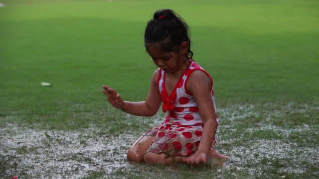 Girl playing in mud in the rainy season