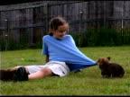 Girl playing with corgi puppies