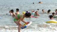 WS ZI MS Girl playing with inflatable ring, others in background swimming / Xiamen, Fujian, China