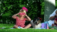 Girl playing with pink cups over eyes sitting next to dog with sunglasses + hat