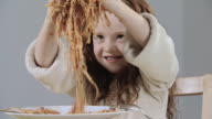 Girl playing with spaghetti