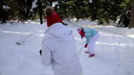 Girl plays with mother in snowballs in the winter park