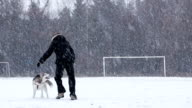 Girl plays with Siberian Husky in winter time.