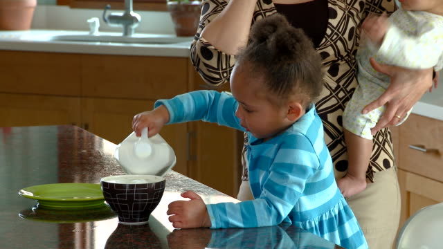 MS TU Girl pouring and spilling milk in bowl while mother holds baby and talks on cell phone / Richmond, Virginia, USA