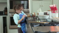 MS Girl (6-7) pouring applesauce into measuring cup, Yarmouth, Maine, USA