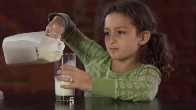 MS Girl (8-9) pouring glass of milk and spilling it / Jersey City, New Jersey, USA