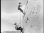 Girl practices tying ropes with group of coed students / close up of girl tying rope around waist / views of students climbing down school dormitory...