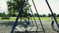 WS PAN SLO MO Girl (10-11) pushing boy (4-5) on swing in park / Orem, Utah, USA