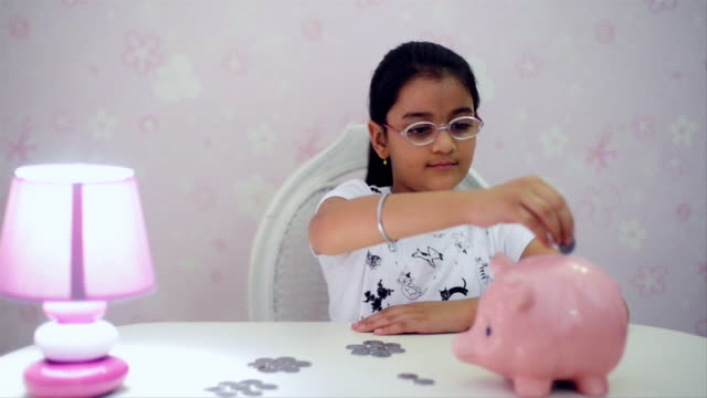 MS Girl putting coins in piggy bank / India