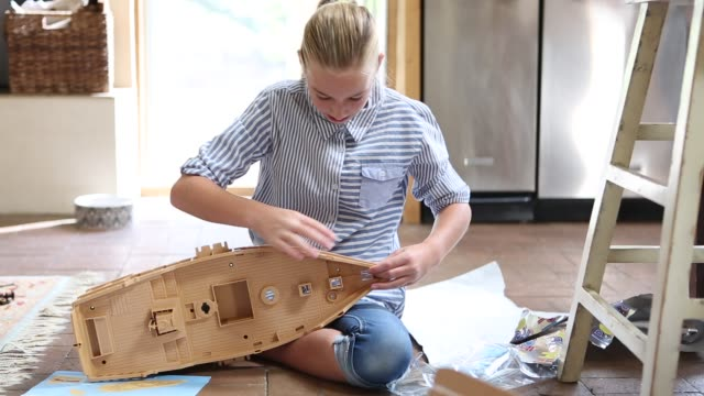 girl putting plastic ship together