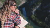 Girl reading a book on the mountain