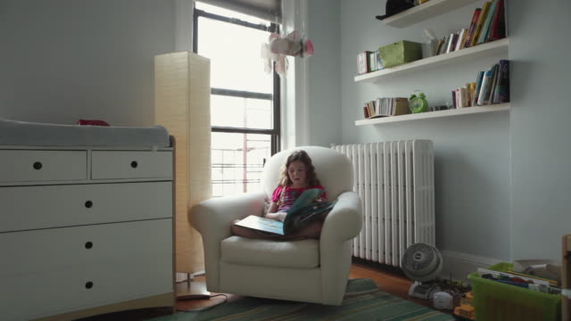 WS Girl (6-7) reading book in kids room / Brooklyn, New York City, USA