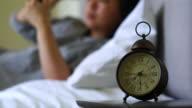 meisje het lezen van de mobiele telefoon op bed, klok op het nachtkastje