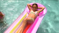HA MS Girl reclining on inflatable raft in pool while other girls swim nearby / Sherman, CT, USA