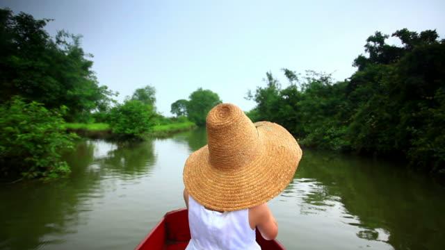 Girl relaxing in boat on  wetlands