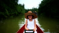 Girl relaxing in boat on wetlands