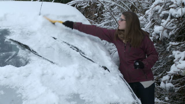 CU Girl removing heavy snow layers from car / Saarburg, Rhineland-Palatinate, Germany