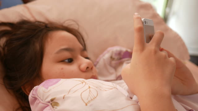 girl rest on bed and using smart phone