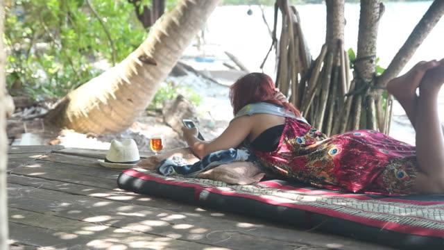 Meisje rusten op strand bed en mobiele telefoon spelen