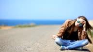 girl resting on the roadside