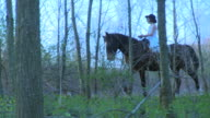 Girl Rides Through Woods on Horse
