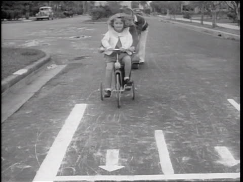 B/W 1936 girl riding tricycle pointing at offscreen toy traffic light + stopping at tiny crosswalk