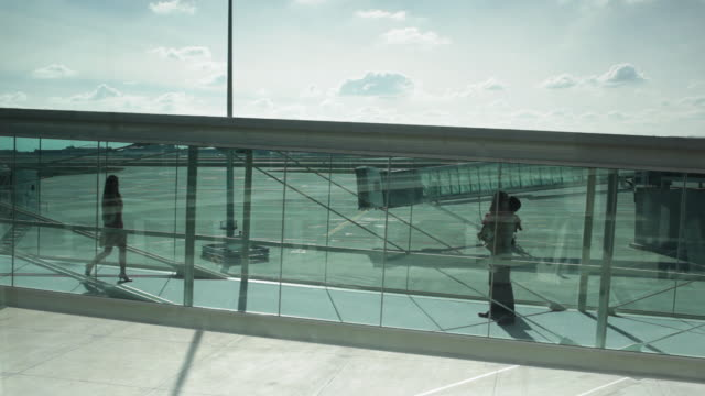 WS Girl (6-7) running along glass walkway into daddy's arms with mummy in tow / Toulouse, Haute-Garonne, France