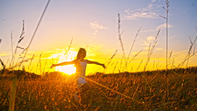 SLO MO Girl Running In A Meadow At Sunset