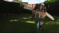 REAR POV Girl running in yard inside cardboard airplane / Great Yarmouth, England, United Kingdom