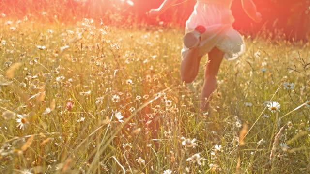 SLO MO TS Girl running through high grass in sunshine