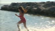 MS PAN Girl (8-9) running through shallow water on beach, Eastville, Virginia, USA