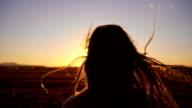 SLO MO Girl running toward the sun at sunset