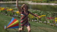 SLO MO MS DS Girl (12-13) running with kite in park / Utah, USA