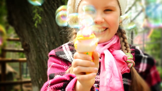 Girl shooting with bubbles gun - HD, NTSC