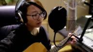 Girl singing and playing guitar in recording studio