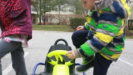 Girl sits in gocart and realizes it doesn't work then boy gets in and he realizes it doesn't work then he uses his feet to back it out of the parking space then father pushes son in gocart.