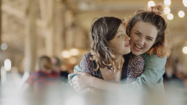 MS SLO MO. Girl sitting alone in restaurant is surprised by a hug from her sister.
