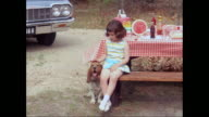 MS Girl sitting at picnic table petting dog / United States