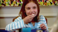 CU, Girl (10-11) sitting at table and eating pop corn