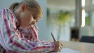 MS Girl (10-11) sitting at table, writing in notebook / Kleinmachnow, Brandenburg, Germany