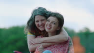 MS SLO MO. Girl sitting in lawn chair by campfire is surprised by hug from mom and smiles at camera.