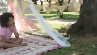 Girl sitting in play tent in garden, thinking and looking at camera