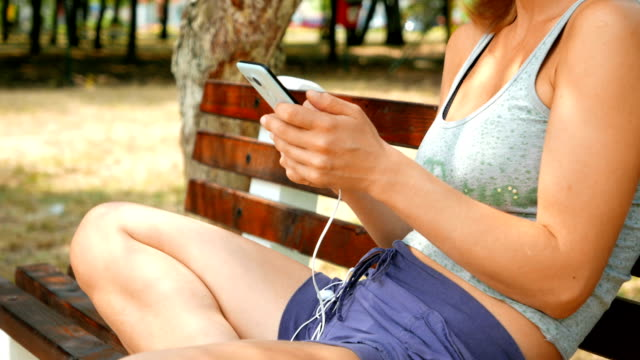 Girl sitting on a bench in the park and using her smart phone