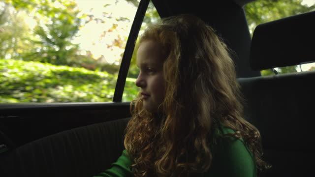 MS Girl (10-11) sitting on back seat of car and enjoying ride / Atlanta, Georgia, USA