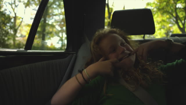 MS Girl (10-11) sitting on back seat of car and pulling funny faces / Atlanta, Georgia, USA