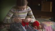 MS PAN Girl (10-11) sitting on bed crocheting heart / Newark, Illinois, USA