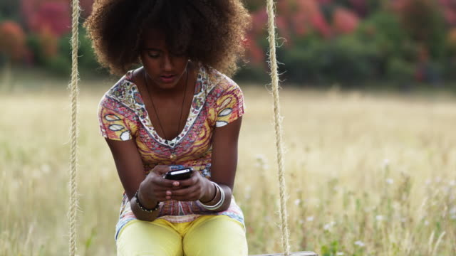 MS TU Girl (12-13) sitting on swing and text messaging in field / South Fork, Utah, USA