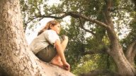 MS LA Girl (6-7) sitting on tree, Flagstaff, Arizona, USA