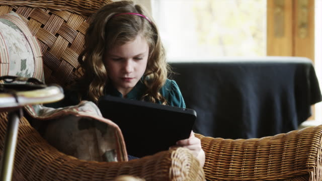 MS ZI Girl (8-9) sitting on wicker armchair and using digital tablet / Cedar Hills, Utah, USA