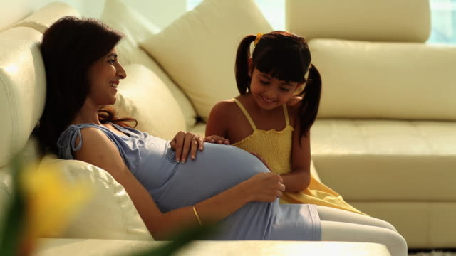 Girl sitting with her pregnant mother